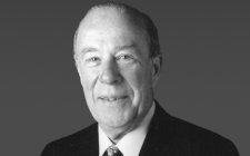 George P. Shultz Wearing A Suit And Tie Smiling And Looking At The Camera