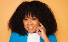 Phoebe Robinson Wearing A Blue Shirt Talking On A Cell Phone